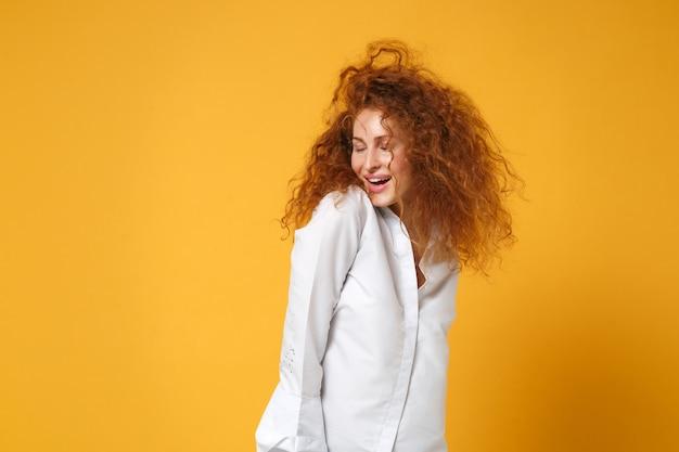 Ontspannen vrolijke prachtige jonge roodharige vrouw meisje in wit overhemd poseren geïsoleerd op geel oranje muur