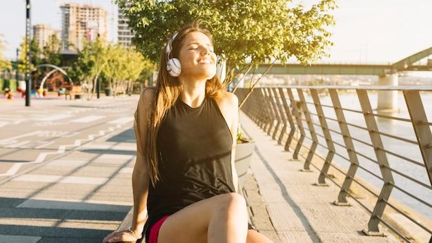 Ontspannen vrouw die aan muziek op hoofdtelefoon in openlucht luisteren