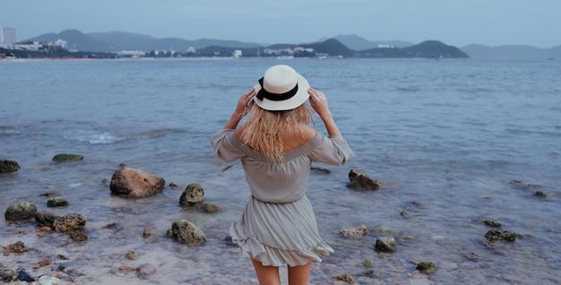 Ontspannen vrouw die van oceaanbaai, vrijheid en het leven genieten bij mooie strandkustlijn in winderig bewolkt weer. jonge dame die zich vrij, ontspannen en gelukkig voelt. concept van vakanties, vrijheid, geluk, plezier
