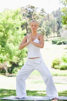 Ontspannen vrouw die yogaoefeningen in het park doet
