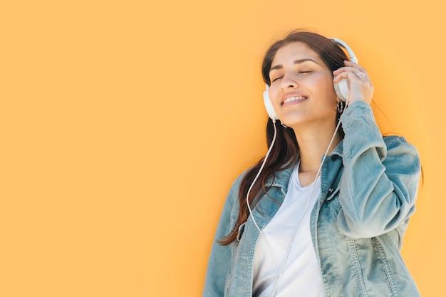 Ontspannen vrouw het luisteren muziek tegen gele achtergrond
