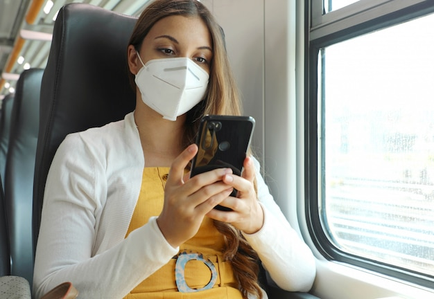 Ontspannen vrouw met kn95 ffp2-gezichtsmasker met behulp van smartphone-app.