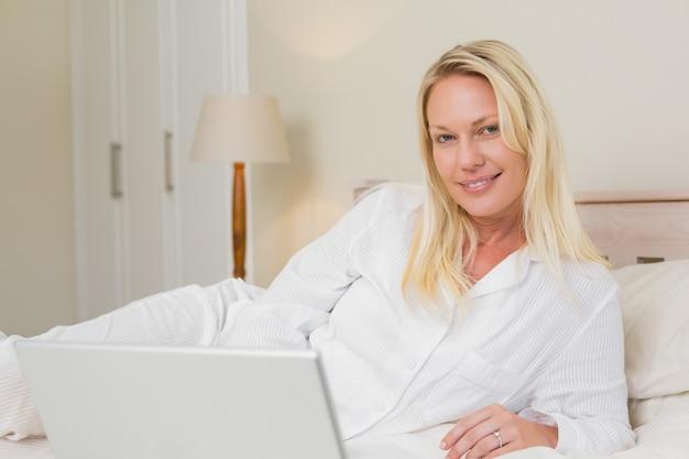 Ontspannen vrouw met laptop in bed