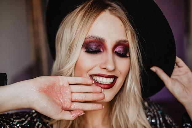 Ontspannen vrouwelijk model met glanzende make-up lachend met gesloten ogen. blij prachtig meisje met lang blond haar poseren in hoed.