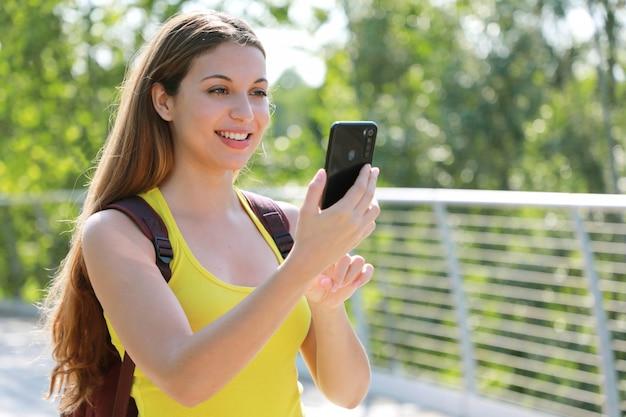 Ontspannen vrouwelijke wandelaar die haar slimme telefoon controleert.