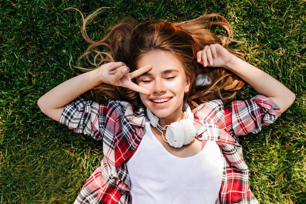 Ontspannen wit meisje liggend op gazon met vredesteken. overhead schot van een behoorlijk goedgehumeurde vrouw.