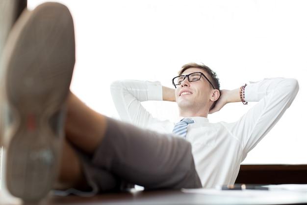 Ontspannen zakenman zitten met benen op bureau