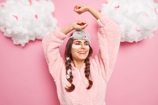 Ontspannen zorgeloze jonge vrouw steekt handen op, voelt zich blij en ontspannen na het ontwaken
