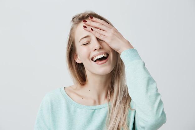 Ontspannen, zorgeloze vrouw met blond haar, ogen sluitend en breed glimlachend, vrijetijdskleding dragend, hand op hoofd houdend, haar ogen sluitend droomend over iets aangenaams. vreugde en emoties