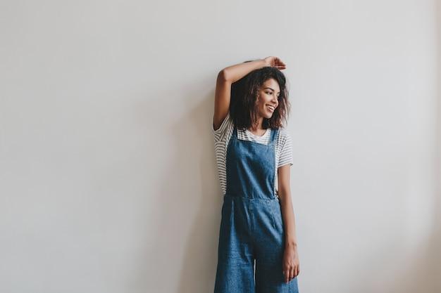 Ontspannen zwart meisje in vintage denim overall poseren met hand omhoog naast witte muur