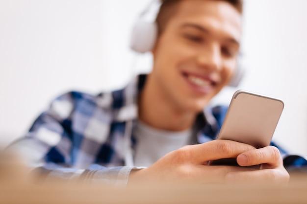 Ontspannend. aantrekkelijke uitbundige blonde jongen glimlachend en koptelefoon dragen en luisteren naar muziek en zijn moderne telefoon vast te houden