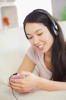 Ontspannend aziatisch meisje die op de bank liggen en aan muziek met smartphone luisteren