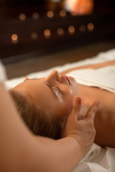 Ontspannende massage. aantrekkelijke onberispelijke dame met vastgebonden haar die slaapt tijdens gezichtsmassage in professioneel spa-centrum-
