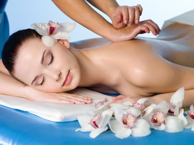Ontspannende massage van rug voor jonge mooie vrouw in spa salon - horizontaal