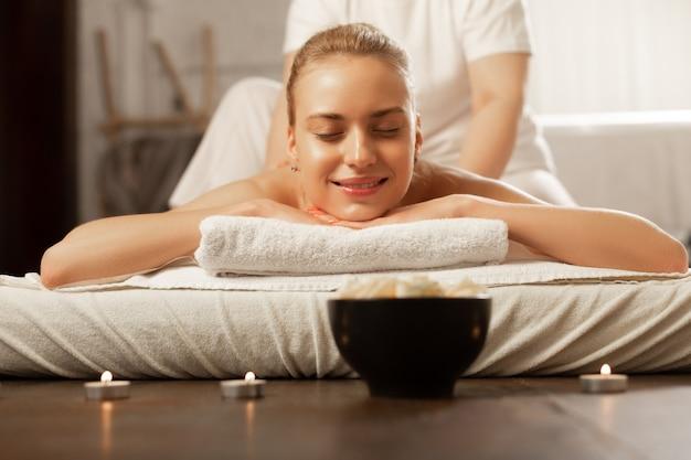 Ontspannende massage. vrolijke aantrekkelijke dame die het hoofd op verbonden handen legt tijdens massage terwijl de meester met haar rug omgaat