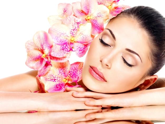 Ontspannende mooie vrouw met een gezonde huid en roze bloemen geïsoleerd op wit