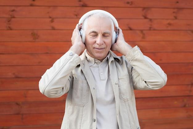 Ontspannende muziektijd. het portret van de hogere mens die in hoofdtelefoons aan muziek luisteren die ogen houden sloot terwijl status tegen houten muurachtergrond