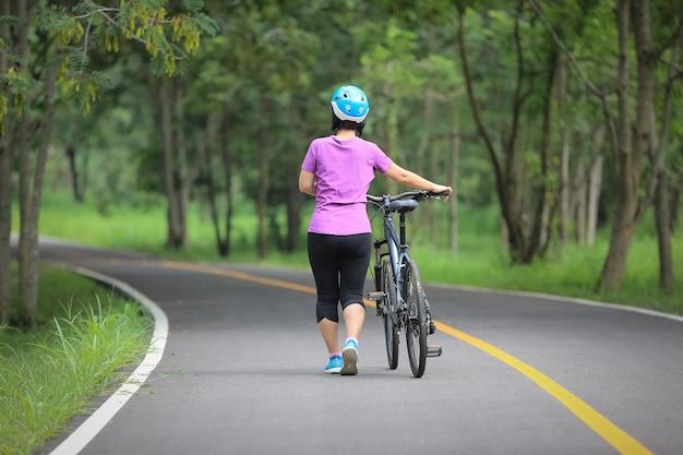 Ontspannende oefening van middelbare leeftijd met fiets in park