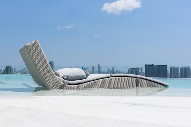 Ontspannende of vrije tijd bed in zwembad met blauwe lucht en wolken