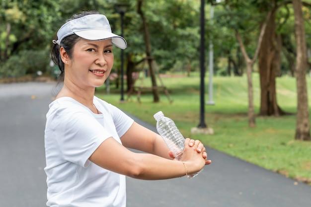Ontspannende tijd. aziatische glimlachende hogere vrouw die zoet water in de zomer drinken bij het park.