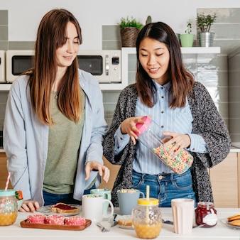 Ontspannende vrolijke meisjes koken ontbijt