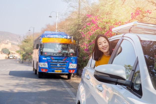 Ontspannende vrouw op de zomer roadtrip die uit het concept van de de reisvakantie van het autoraam leunen.