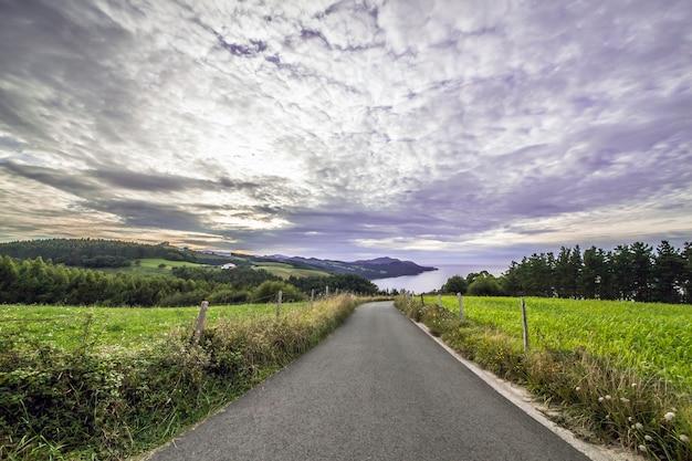Ontspannende weg omringd door veel flora en erg kleurrijk die ons naar de zee leidt met een bewolkte maar spectaculaire lucht.