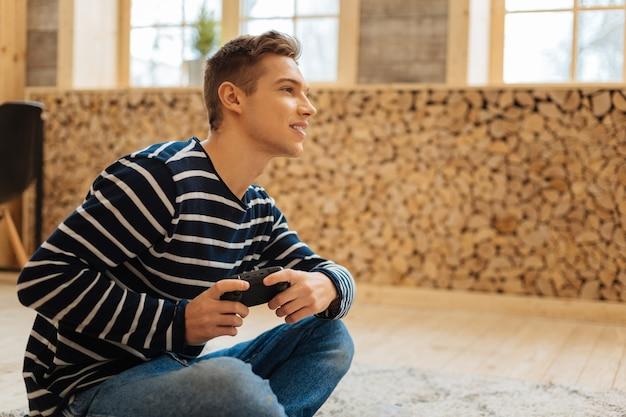 Ontspanning dag. aantrekkelijke alerte blonde jonge man glimlachend en met een afstandsbediening voor games zittend op de vloer