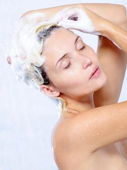 Ontspanning en plezier krijgen voor jonge vrouw die een douche neemt