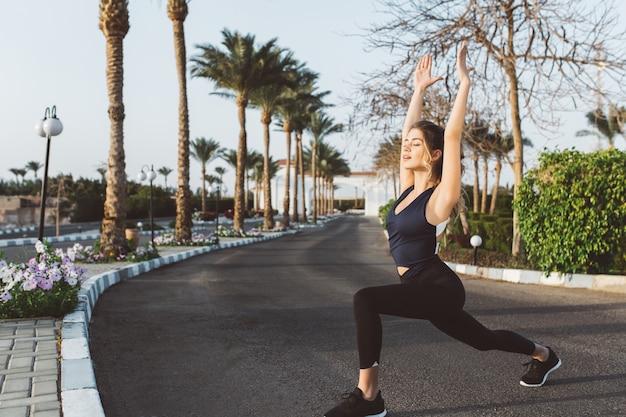 Ontspanning van jonge aantrekkelijke jonge vrouw die zich uitstrekt op straat in tropische stad. resort, training, opgewekte stemming, fitness, yoga, motivatie.
