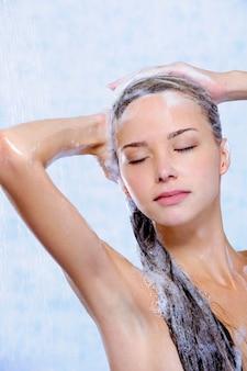 Ontspanning van jonge vrouw die douche neemt - close-upportret
