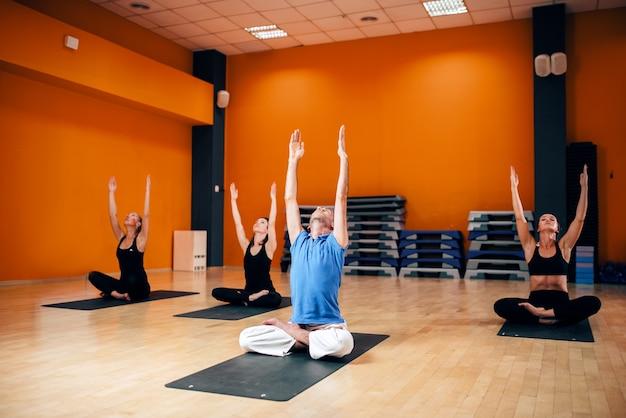 Ontspanning, vrouwelijke groep met trainer zittend in yoga pose, trainen in de sportschool. yogi binnen