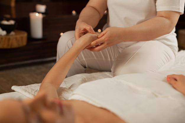 Ontspanningsmassage ontvangen. ervaren massagemeester die tijdens een aangename procedure op stippen op de hand van haar cliënt drukt