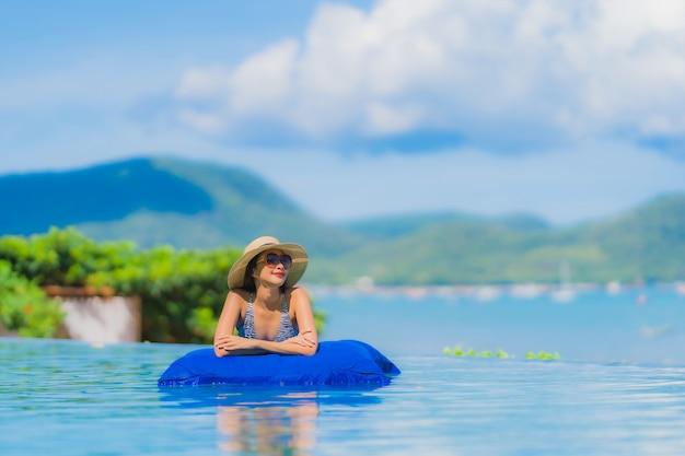 Ontspant de gelukkige jonge glimlach van de portret mooie jonge aziatische vrouw in zwembad bij het overzeese oceaanstrand van de hoteltoevlucht neary op blauwe hemel
