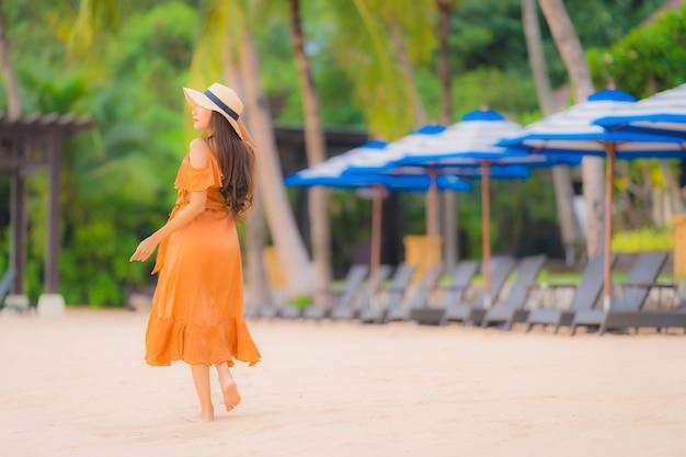 Ontspant de gelukkige jonge glimlach van de portret mooie jonge aziatische vrouw op de strand overzeese oceaan