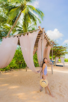 Ontspant de mooie jonge aziatische vrouwen gelukkige glimlach op de tropische strand overzeese oceaan voor vrije tijdsreis