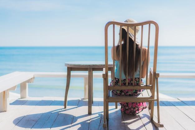 Ontspant de mooie jonge aziatische vrouwen gelukkige glimlach van het portret rond strandoceaan en overzees