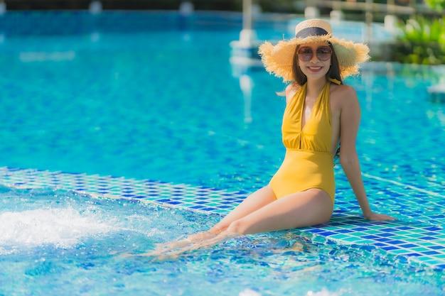 Ontspant de mooie jonge aziatische vrouwen van het portret glimlach en gelukkig rond zwembad in hoteltoevlucht