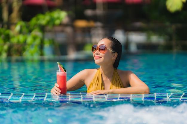Ontspant de mooie jonge aziatische vrouwenvrije tijd glimlach met watermeloensap rond zwembad in hoteltoevlucht