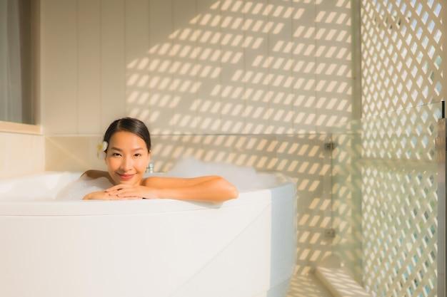 Ontspant de portret jonge aziatische vrouw een bad in badkuip neemt