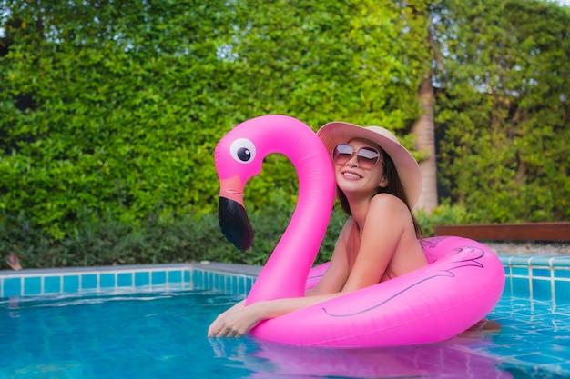 Ontspant de portret jonge aziatische vrouw gelukkige glimlach rond zwembad in hotel