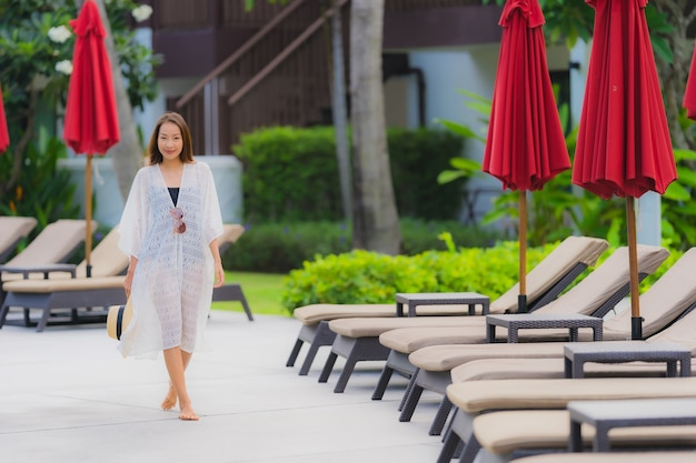 Ontspant de portret jonge aziatische vrouw glimlach gelukkig rond openluchtzwembad in hoteltoevlucht met overzeese oceaanmening