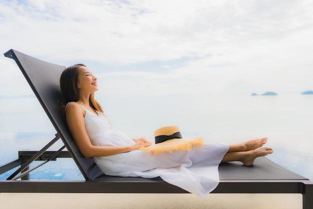 Ontspant de portret jonge aziatische vrouw glimlach gelukkig rond zwembad in hotel en toevlucht