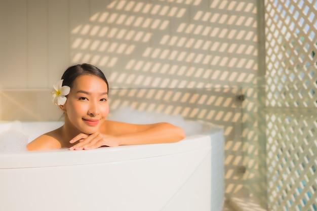 Ontspant de portret jonge aziatische vrouw neemt een bad in badkuip