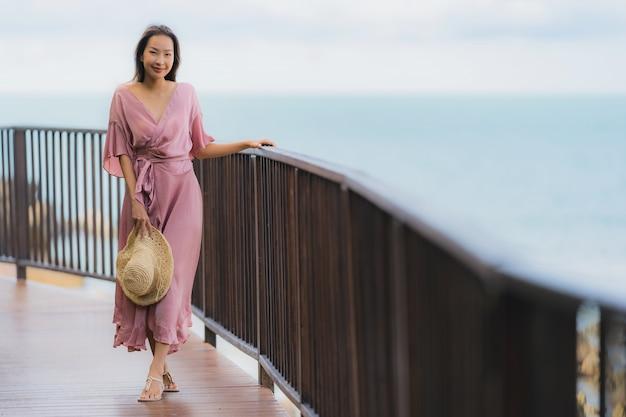 Ontspant de portret mooie jonge aziatische vrouw die overzeese strandoceaan kijken voor in de vakantie van de vakantievakantie
