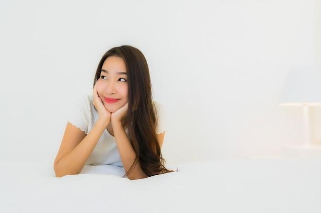 Ontspant de portret mooie jonge aziatische vrouw gelukkige glimlach op bed met witte hoofdkussendeken