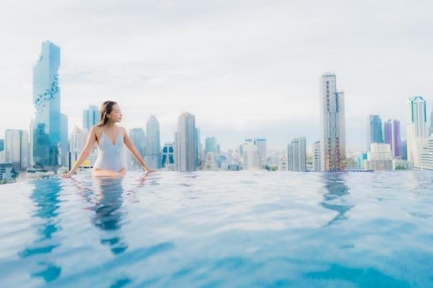 Ontspant de portret mooie jonge aziatische vrouw gelukkige glimlachvrije tijd rond openluchtzwembad