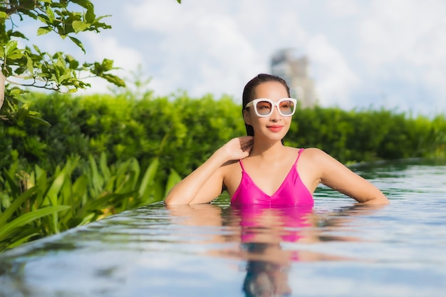 Ontspant de portret mooie jonge aziatische vrouw geniet rond openluchtzwembad in vakantievakantie