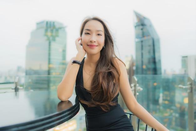 Ontspant de portret mooie jonge aziatische vrouw geniet van restaurant op het dak