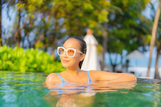 Ontspant de portret mooie jonge aziatische vrouw glimlach geniet van vrije tijd rond zwembad bijna overzees strand oceaanmening op vakantie